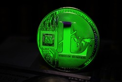 Green Litecoin LTC coin is surrounded by a gloomy background.
