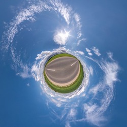 green little planet transformation of spherical panorama 360 degrees. Spherical abstract aerial view in field with clear sky and awesome beautiful clouds. Curvature of space.