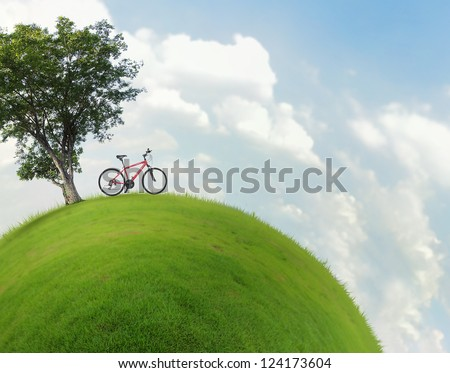 Green little planet with grass on its surface, alone tree and red bicycle near it. Artificial grass added around the surface of planet
