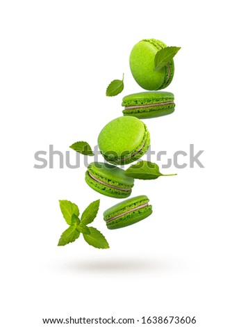 Green macaroons are flying on a white background. Beautiful bright macaroons with mint leaves