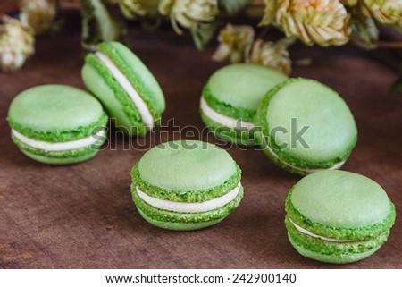 Green macaroons with hop flowers on dark wooden background. Vintage dark scene. Shallow focus