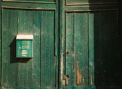 Green mailbox on a green wood door