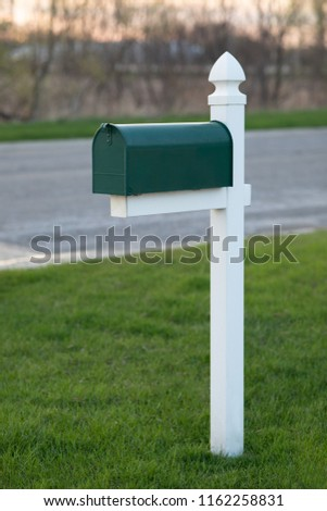 Green mailbox on lawn