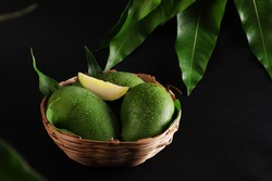 green mango and green leaf on basket and old dark floor background,Group of raw mangoes organic with sour and high vitamin C fruit for healthy.