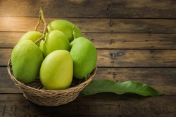 green mango in basket on old wooden floor space for text with dark tone,freshness green mango,group of mangoes.