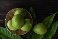Green Mango Raw in basket and leaves top view