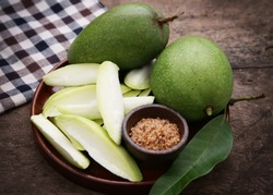 Green mango with chili powder and salt on wooden table.