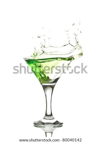 green martini cocktail splashing into glass on white background - stock photo