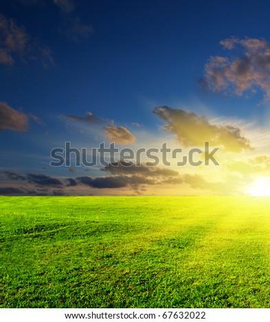 Green meadow and dark sky with sun