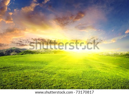 Green meadow during sundown with bright sun