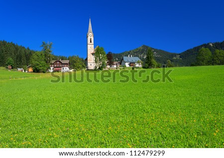 Green meadow in alpine village with church in the distance, Gosau, Austria