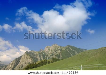Green meadow in mountain with clouds in xinjiang,china