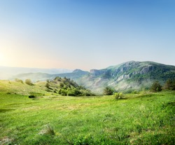 Green meadow on the background of the Crimean mountains