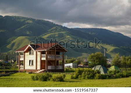 Green meadow with touristic cottage and touristic tents, in countryside and forest growed mountains on the background