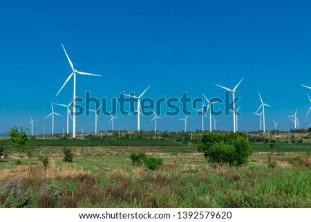 green meadow with Wind turbines generating electricity #1392579620