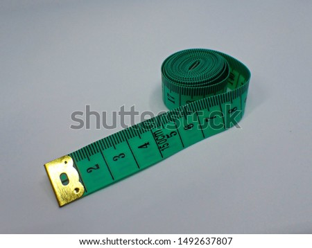 Green measuring tape on a white desk, centimeter side up
