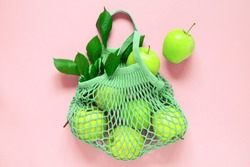 Green mesh bag with fresh apples. Zero waste, eco friendly or plastic free lifestyle concept, copy space