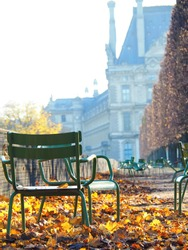 Green metal chairs with yellow leaves near the Louvre museum, Paris