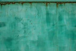 Green metal dirty sheet fence. Rust grunge leaks template blank. Old paint on the fence. Copper abstract wall art
