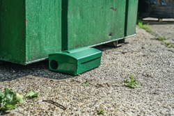 Green Metal external rodent rat bait station outside against a brick wall close up.  Pest Control.