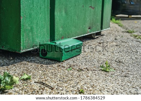 Photo of  Green Metal external rodent rat bait station outside against a brick wall close up.  Pest Control.