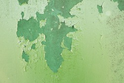 Green metal plate with cracked paint and big paint spots because of time as background, metal wall with rusty spots and cracked paint as texture, toned to color