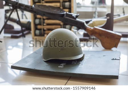 green military helmets, stand in the arms store on the background of machine guns and machine guns.