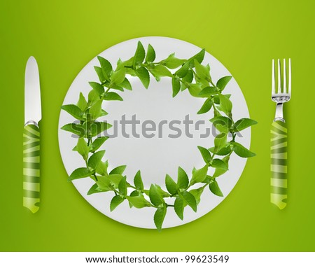 green mint leaves on white plate with knife and fork on blue background.