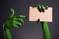 Green monster hand with black nails pointing on blank piece of cardboard, Halloween theme