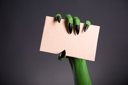 Green monster hand with sharp nails holding blank piece of cardboard, Halloween theme