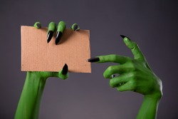 Green monster hands with black long nails pointing on blank piece of cardboard, Halloween theme