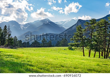 green mountain meadow with mountain range in the background.at Rocky Mountain National Park, Colorado