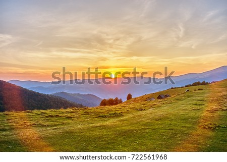 Green mountain peak on a background of beautiful sunset on a blue sky. #722561968