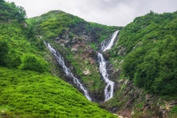 Green mountain range with waterfall and in spring or summer. Powerful stream of mountain river with waterfall covered in fog and clouds. Achipsa falls, Krasnaya Polyana, Sochi, Russia