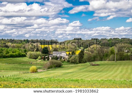 Green mountain valleys and blooming yellow rapeseed fields in the Belgian Ardennes, soft focus. Mountain landscape with green expanses and rural houses on a background of blue sky with low clouds. Photo stock ©