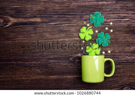 Green mug with four-leaf clover on wooden background. Copy space, top view.  St.Patrick's day holiday symbol.