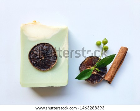 Green natural oil soap and dried slice lemon with herb on white background, cold process, swirl technique, handmade product.