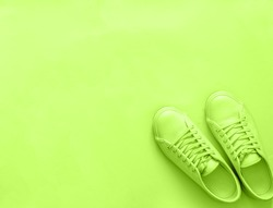 Green neon leather sneakers on green background. Pair of fashion trendy green sport shoes sneakers with copy space for text or design. Overhead shot of new green sneakers,monochrome.Top view, flat lay