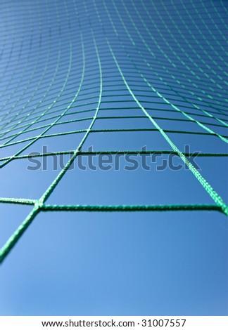 Green net against blue sky.