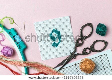 Green number 9 cross-stitch embroidered surrounded by accessories for embroidery: threads of moulin of different colors, needles, scheme, hoop, scissors. Handmade Photo stock ©
