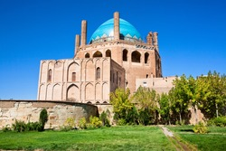 Green oasis with trees and historical 14 century blue domed mausoleum Dome of Soltaniyeh near Zanjan city, Iran. UNESCO World Heritage Site, so called Iranian Taj Mahal, erected from 1302 to 1312 AD.