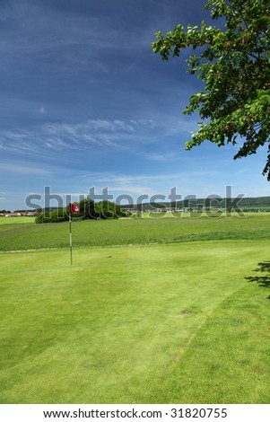 green of a beautiful golf course with dramatic summer sky