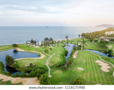 Green of the golf course, Built adjacent to the beach and the sea. Is a field with Atmosphere SpontaneityAnd relax. There is a mountain and blue sky at background. #1118175980
