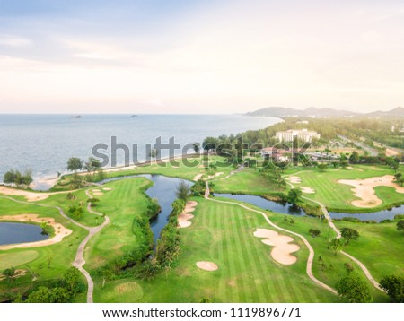 Green of the golf course, Built adjacent to the beach and the sea. Is a field with Atmosphere SpontaneityAnd relax. There is a mountain and blue sky at background. #1119896771