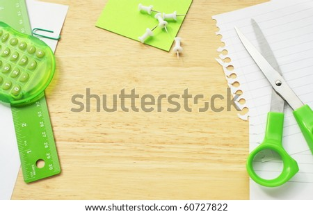 Green office stationary and equipment on a wood desktop background