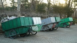 Green old handcarts on the road in the park in winter