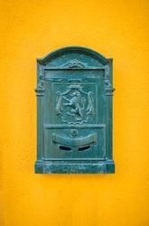 Green, old, vintage mailbox hanging on the yellow wall