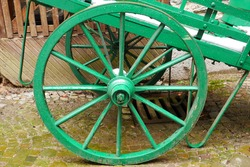 green old wagon wheel of a medieval handcart with snow on the cart