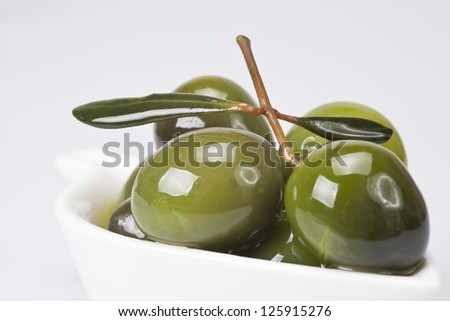 Green olives in a china spoon over a white background
