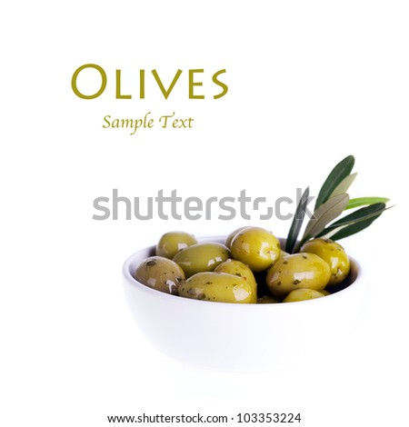 Green olives in a white ceramic bowl with olive branch. Isolated on white with space for text.